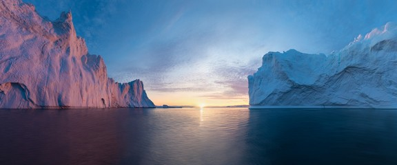 Papiers peints Antarctique Early morning summer alpenglow lighting up icebergs during midnight season. Ilulissat, Greenland. Summer Midnight Sun and icebergs. Blue ice in icefjord. Affected by climate change and global warming.