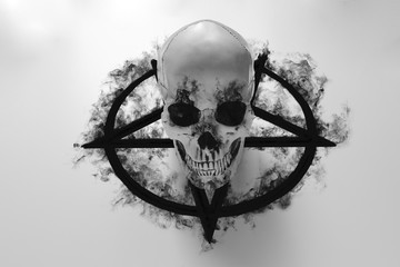 White human skull on top of black pentagram on white background with black smoke