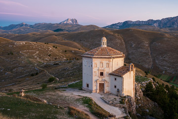 Fotobehang Purper Beautiful chapel Chiesa di Santa Maria della Pietà at dawn before sunrise with barren landscape and mountain of Corno Grande in background, Rocca Calascio, Abruzzo, Italy