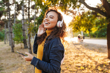 Beautiful young curly woman listening music