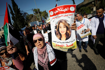 Demonstrator holds a picture of Jordanian citizen Hiba Labadi during a protest in Ramallah in the Israeli-occupied West Bank