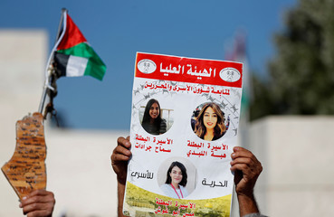 Demonstrator holds a poster showing Jordanian citizen Hiba Labadi and other Palestinian prisoners during a protest in Ramallah in the Israeli-occupied West Bank
