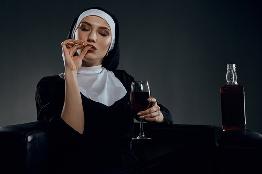 Cropped half-turn shot of a nun, sitting on a black chair. She's wearing dark nun's clothing. The nun is smoking and holding glass of wine in her hand. There is a bottle with alcohol on chair armrest.