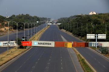 Shipping containers used to block the road leading towards the red zone are seen before what participants call a Freedom March in Islamabad