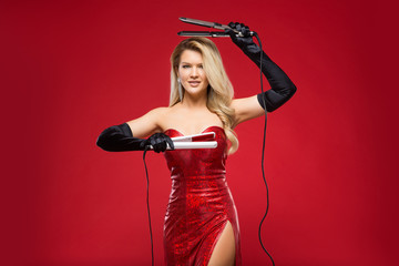 girl hairdresser with curling irons in hands in a red dress on a red background