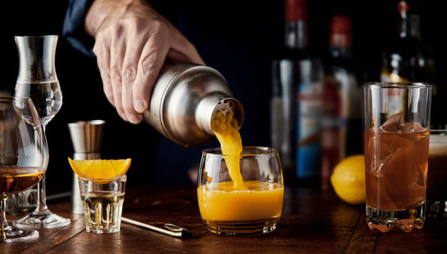 Barman serving a shaken alcoholic orange cocktail