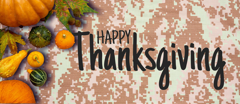 Happy Thanksgiving flat lay with colorful pumpkins and fruits on army digital pattern textile