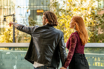 Couple looking and pointing into the cityscape