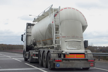 Cement truck with a round barrel semi trailer moving on asphalted highway road in autumn day, Logistics, bulk material road carriage, side rear view