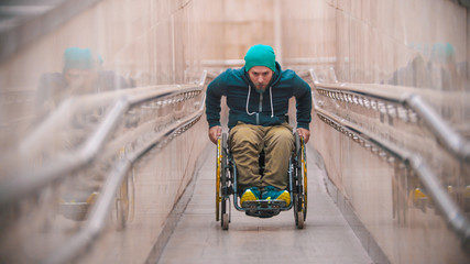 Disabled man in wheelchair getting up on the long special ramp