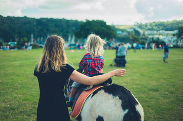 Little toddler riding a donkey at the fair