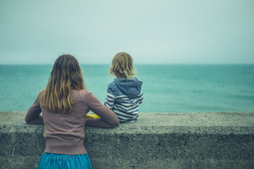 Mother and toddler relaxing on wall by the sea