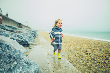 Little toddler running and playing on a rocky beach in the rain