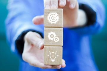 Man hand arranging wood block with icon goal strategy and action business plan.