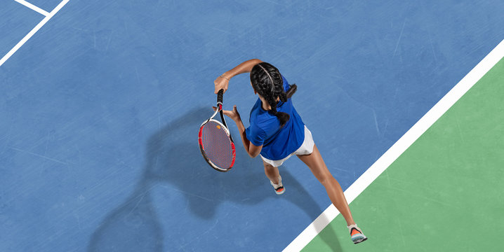 Young caucasian brunette woman in blue shirt playing tennis at the court. Hits ball with racket, outdoors. Youth, flexibility, power, energy. Copyspace. Top view. Motion, action, healthy lifestyle.
