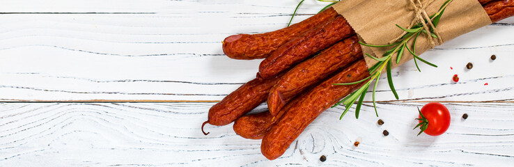 Kabanos or Cabanossi Thin Dry Smoked Polish Sausage on White Wooden Background. Selective focus.