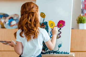 back view of redhead child painting on canvas in art school