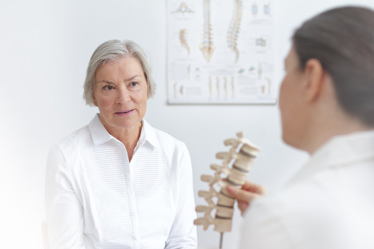 Aging and back pain concept: doctor of rheumatolgy showing her senior patient a slipped disk on a backbone model.