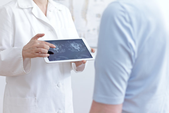 Back pain concept: doctor with tablet pc showing her patient cat scan images of her lumbar spines.