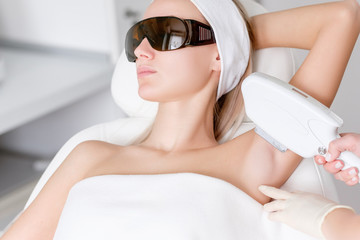 Young pretty caucasian woman in dark glasses is undergoing photoepilation procedure in the salon. Concept removal of unwanted hair from body skin