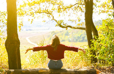 Stylish hipster girl is sitting in forest. Happy woman enjoying autumn nature. Beautiful landscape. Lifestyle travel concept. Dark red sweater. Yellow leaves on trees. View from mountain hill. Wall mural