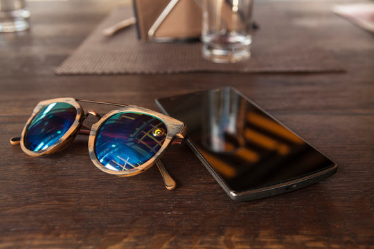 Smart phone and hipster sunglasses on wood bar table, blank screen and selected focus
