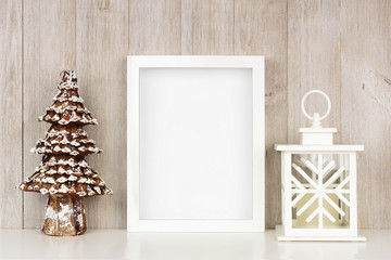 Mock up white frame with Christmas tree and lantern decor on a shelf. Portrait frame against a rustic gray wood wall.