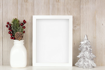 Mock up white frame with Christmas branches and silver tree on a shelf. Portrait frame against a rustic gray wood wall.