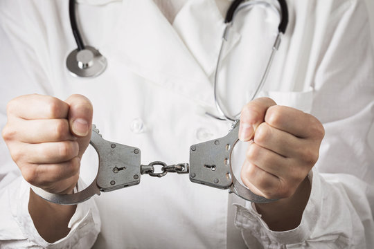 Handcuffed doctor. Medical malpractice and error concept