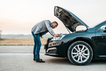 Elegant middle age business man trying to fix car breakdown or engine failure and waiting for towing service for help car accident on the road. Roadside assistance concept.