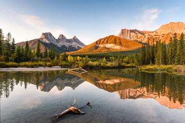 Scenery of Three sisters mountain reflection on pond at sunrise in autumn at Banff national park