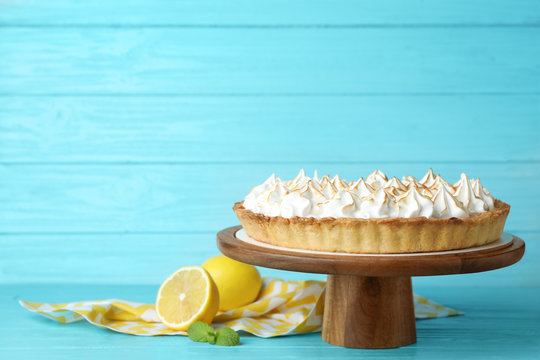 Stand with delicious lemon meringue pie on blue wooden table, space for text