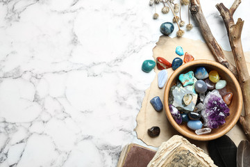 Flat lay composition with different gemstones on white marble background. Space for text