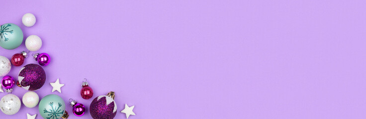 Modern pastel Christmas bauble corner border banner over a light purple background with copy space