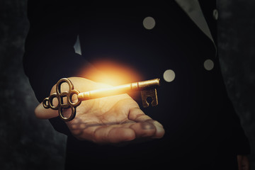 Close up image of a business person holding a shining key. Success business concept