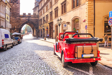 City landscape - view of a vintage car and entrance to Charles Bridge, in the historical center of Prague, Czech Republic