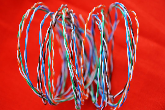 Telephone or computer network cable twisted pair twisted into a spiral. On red background. Selective soft focus