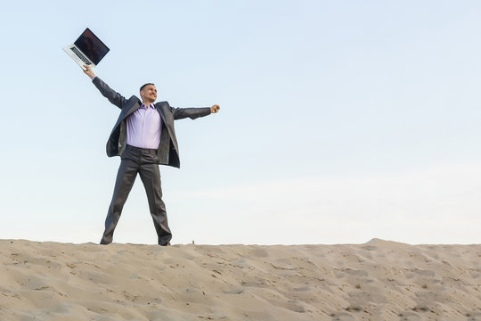 Businessman working and using a laptop and phone in a desert