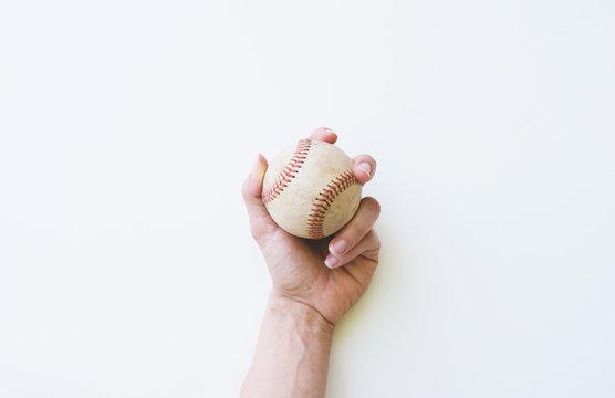Hand holding old used baseball, isolated on white background.
