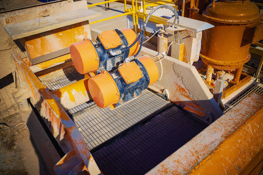 Shale shaker on an offshore oil rig. Shale shaker screen close up view with drill cutting flow out from oil base mud. Separators are end. Equipment for oil separation.