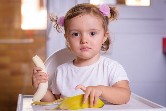Cute baby 1,4 years old sitting on high children chair and eating a banana alone in white kitchen