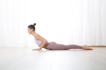 Fotomurales - Portrait of gorgeous active sporty young woman practicing yoga in studio. Beautiful girl practice Bhujangasana, cobra yoga pose. Healthy active lifestyle, working out indoors in gym.