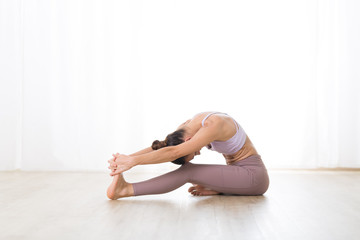 Portrait of gorgeous active sporty young woman practicing yoga in studio. Beautiful girl practice Janushiransa with Paschimotthanasana, head to knee with streching yoga pose.