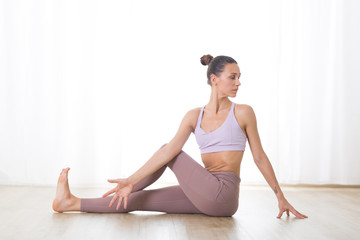 Fotomurales - Portrait of gorgeous active sporty young woman practicing yoga in studio. Beautiful girl practice Ardha Matsyendrasana, spine twisting yoga pose. Healthy active lifestyle, working out indoors in gym.