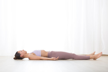 Fotomurales - Portrait of gorgeous active sporty young woman practicing yoga in studio. Beautiful girl relaxing in Savasana, corpse pose. Healthy active lifestyle, working out indoors in gym.