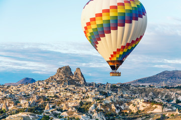 Keuken foto achterwand Ballon A single bright hot air balloon floats over the cave homes and town in Cappadoccia, Turkey.