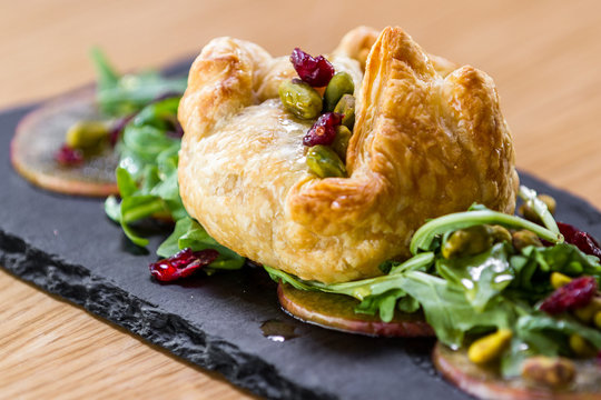 Baked brie inside of a puff pastry served with greens and seasonal fruit