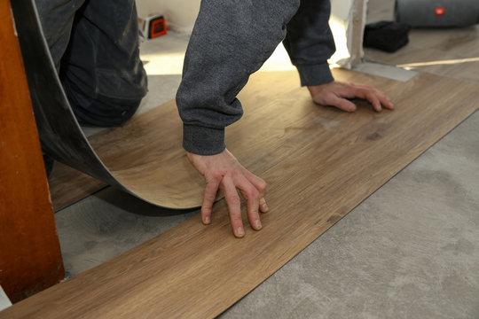 The worker installing new vinyl tile floor