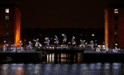 An car drives past an installation called 'Run Beyond' which forms part of the River of Light festival in Liverpool, Britain