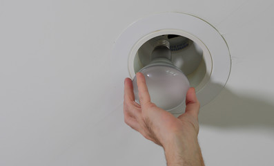 Fototapeta Electrician installing new light bulb in recessed ceiling light fixture. Man replacing burned out incandescent light bulb. obraz